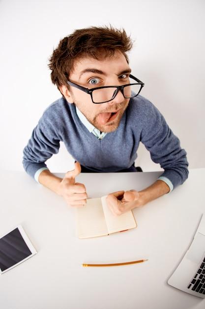 Веселый и игривый молодой бизнесмен в очках, садится за рабочий стол, черпает вдохновение, записывает идеи в блокнот, показывает язык и показывает пальцем Бесплатные Фотографии