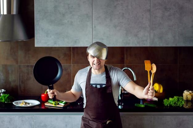 面白い怒っている敗者の男性男性の頭に金属鍋、フライパン、木製の調理器具を調理しようとすると、失敗し、灰色のモダンなロフトキッチンで叫ぶ。キッチンのコンセプトに失敗した学士。 Premium写真