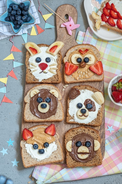 Funny animal faces toasts with butter, banana, strawberry, and blueberry Premium Photo