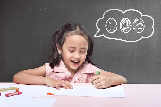 Funny asian little girl with crayon drawing easter egg Premium Photo