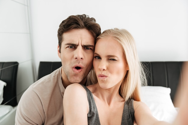 Funny attractive lovers making selfie and grimacing in the morning Free Photo