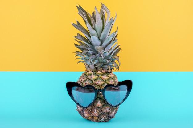 Забавный привлекательный ананас в стильных очках на желто-синем фоне. концепция летних каникул. Premium Фотографии