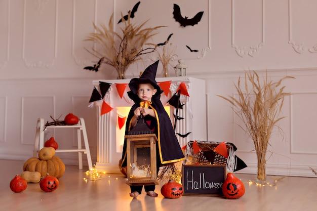 カボチャのジャックとほうきを屋内でハロウィーンの魔女の衣装で面白い男の子 Premium写真