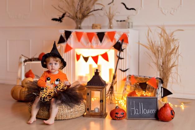 カボチャのジャックとほうきを屋内でハロウィーンの魔女の衣装で面白い赤ちゃん女の子 Premium写真
