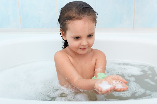 Funny baby girl playing with water and foam in big bath tub Free Photo
