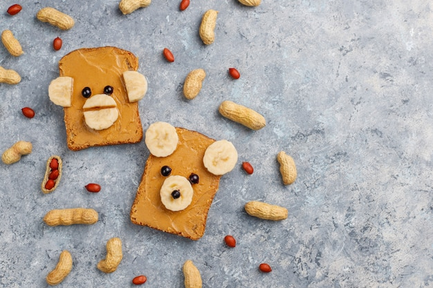 Funny bear and monkey face sandwich with peanut butter, banana and black currant,peanuts on grey concrete background Free Photo