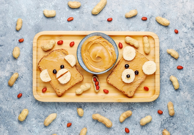 Funny bear and monkey face sandwich with peanut butter, banana and black currant, peanuts, top view Free Photo