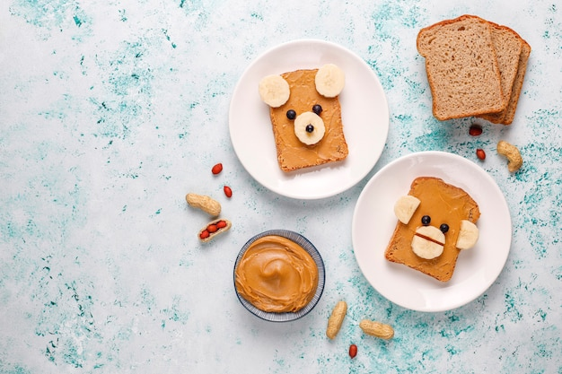 Funny bear and monkey face sandwich with peanut butter, banana and black currant, top view Free Photo