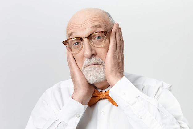 Забавный бородатый пожилой мужчина в стильных очках, страдающий от ужасной зубной боли, держится руками за щеки, выпуская голубые глаза. испуганный старший мужчина выражает шок и удивление Бесплатные Фотографии