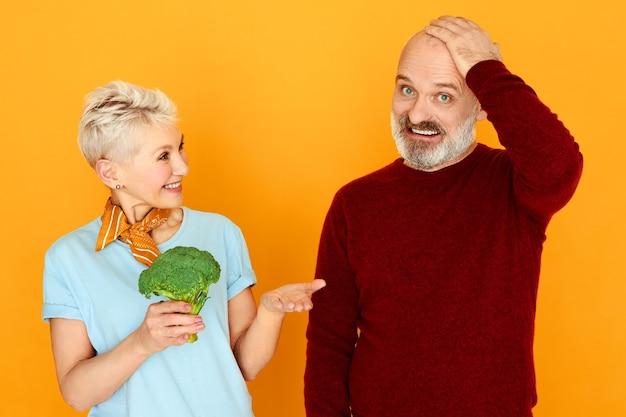 困惑した表情で胸に手をつないでいるおかしなひげを生やした男性年金受給者は、妻が彼に提供しているブロッコリーを食べたくない。 無料写真
