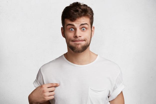 Il maschio barbuto divertente preme le labbra, indica la maglietta casuale in bianco Foto Gratuite