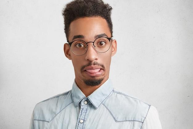 Забавный бородатый самец с привлекательной внешностью дурит, показывает язык, с удивленным выражением лица Бесплатные Фотографии