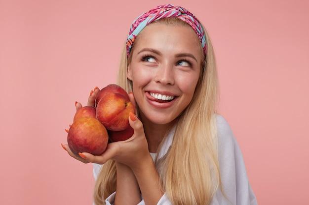 桃を手にポーズをとって、冗談めかして脇を見て、舌を抜く面白い美しい金髪の女性 無料写真