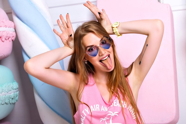 Funny beautiful crazy woman posing on wall of big colorful fake sweets, making grimace face, showing tongue. brightful emotions, trendy pink clothes, happy blonde girl Free Photo