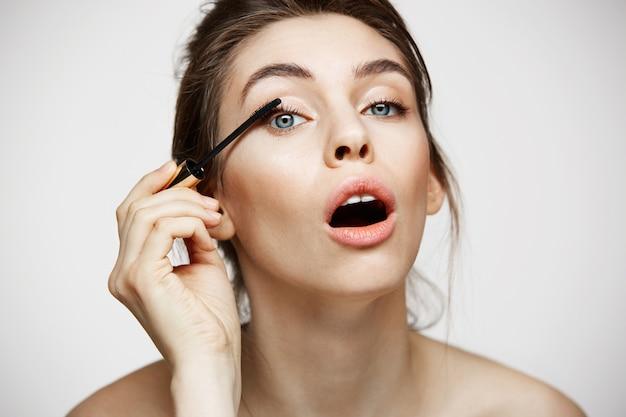 Смешные красивые ресницы краски девушки при раскрытый рот смотря камеру над белой предпосылкой. красота здоровье и косметология концепции. Бесплатные Фотографии