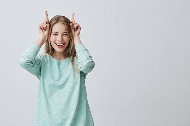 頭の上に広く指を保持して笑っている面白いブロンドの女性。角のジェスチャー 無料写真