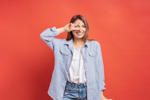 Funny, carefree girl having fun isolated on a red wall Free Photo
