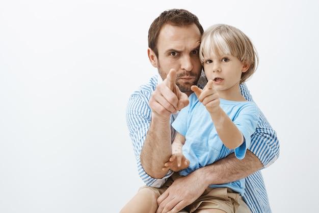 Забавный заботливый европейский отец, держащий и обнимающий симпатичного маленького сына с витилиго, указывая, хмурясь и корча рожи Бесплатные Фотографии
