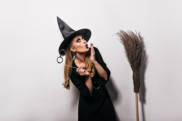 Смешная кавказская девушка позирует в костюме ведьмы на карнавале. длинноволосая женщина в волшебной шляпе, стоя на белой стене с метлой. Бесплатные Фотографии