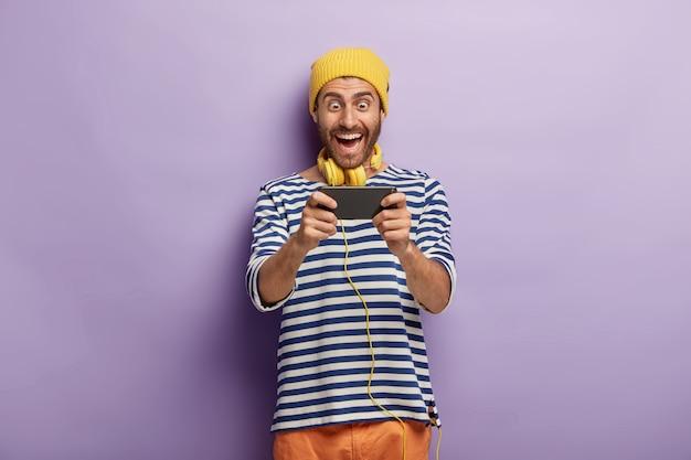 Divertente giocatore maschio allegro gioca ai videogiochi tramite smartphone, indossa un cappello giallo e un maglione a strisce, essendo dipendente dalle moderne tecnologie, isolato sul muro viola, controlla la nuova applicazione Foto Gratuite