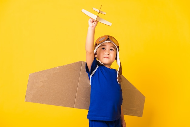 Funny child boy smile wear pilot hat play and goggles with toy cardboard airplane wings fly hold plane toy Premium Photo