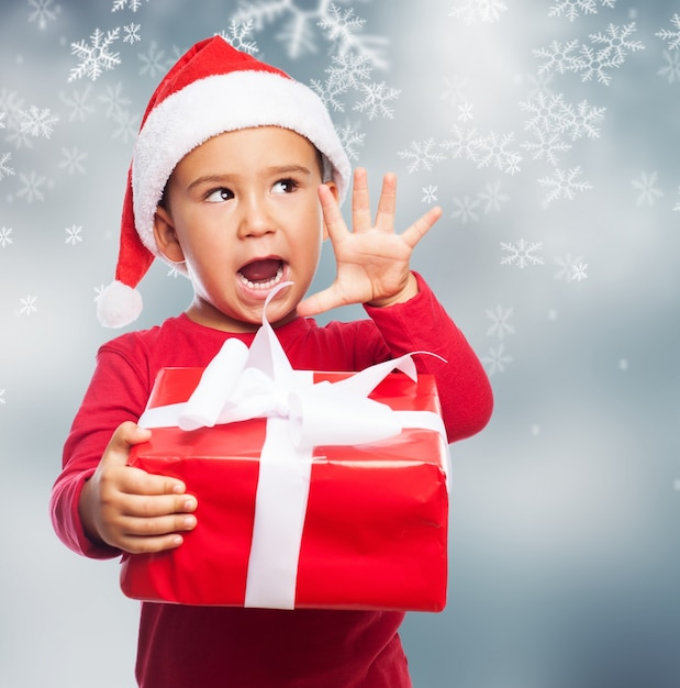 Funny child holding a christmas gift with his right hand Free Photo