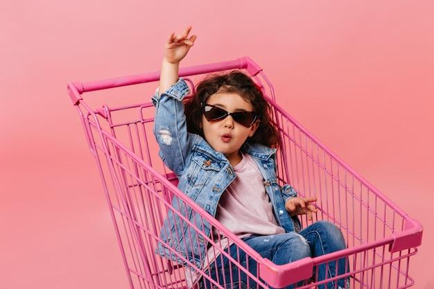 Смешной ребенок в солнечных очках, сидя в корзине. студия сняла счастливую маленькую девочку в джинсовой куртке. Бесплатные Фотографии