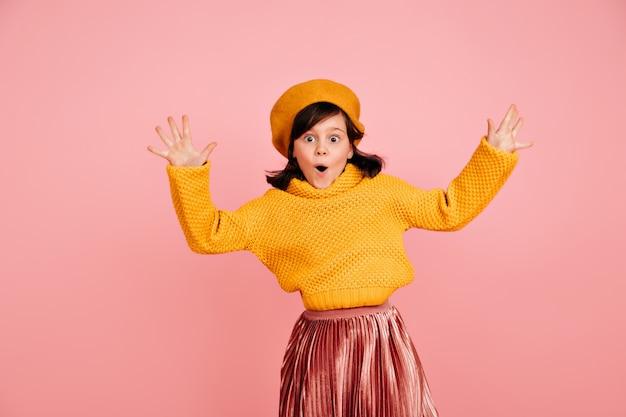 手を上げてジャンプする面白い子。黄色いセーターを着たのんきなプレティーンの女の子。 無料写真