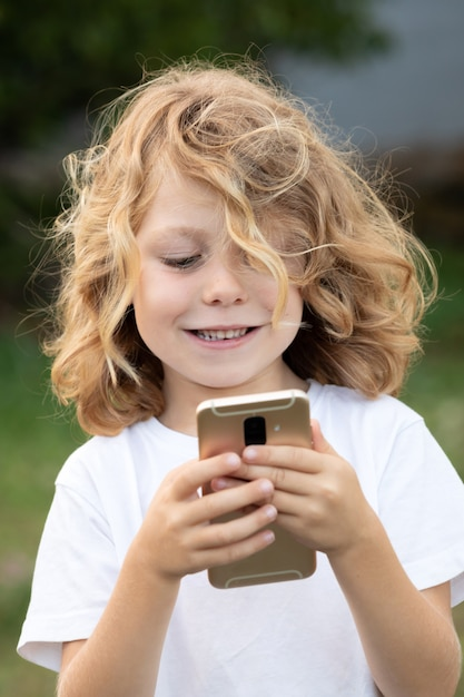 Funny child with long hair holding a mobile Premium Photo