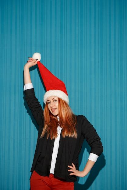 Divertente ragazza di natale che indossa un cappello da babbo natale su sfondo blu studio Foto Gratuite