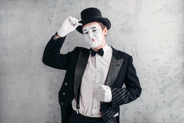 Funny comedy actor with makeup face. pantomime in suit, gloves and hat. Premium Photo
