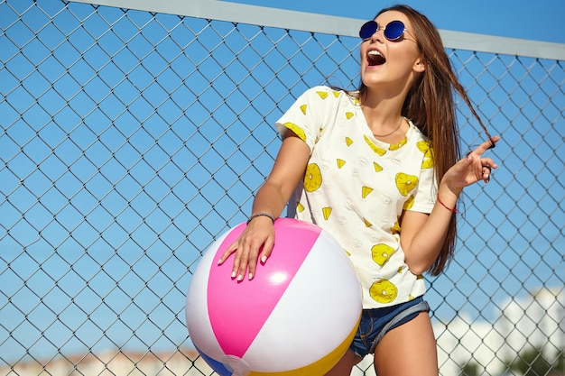 Funny crazy glamor stylish smiling beautiful young woman model in bright hipster summer casual clothes posing in the street behind iron grating and blue sky. playing with colorful inflatable ball floa Free Photo