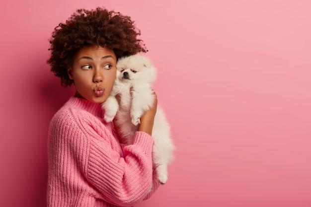 Забавная кудрявая женщина держит губы сложенными, в свободное время проводит с симпатичным щенком миниатюрной породы, держит шпица близко к лицу Бесплатные Фотографии