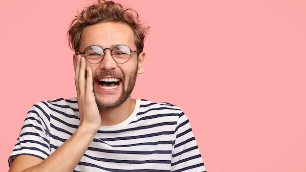 面白い巻き毛の男は幸せに笑い、頬に触れ、面白いプログラムを見て、カジュアルなストライプのtシャツを着て、ピンクの壁に立っています。 無料写真