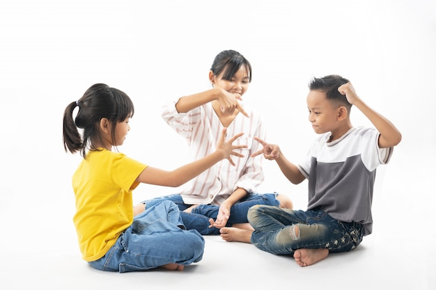 Funny and cute group of asian children playing rock paper scissors by sister being referee. Premium Photo
