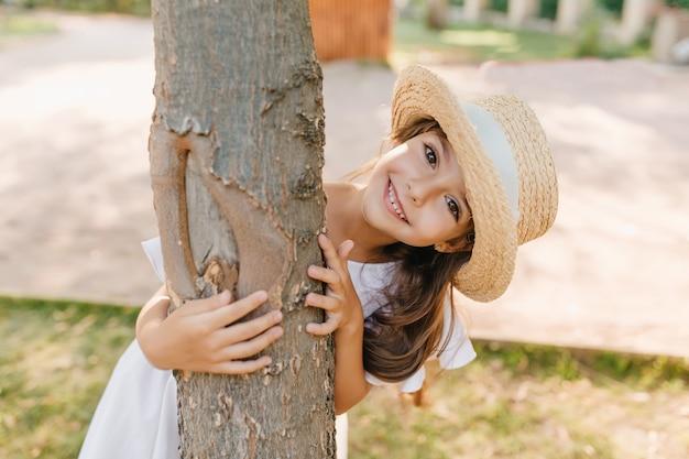公園で木を抱きしめる大きな目と笑顔を持つ面白い黒髪の子供。夏休みを楽しんでいる麦わら帽子の幸せな少女の屋外の肖像画。 無料写真