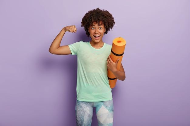 面白い暗い肌の女性は腕を上げ、トレーニング後に筋肉を見せ、カレマットを保持し、コーチと一緒にジムで定期的にトレーニングをし、スポーツウェアを着て、紫色の壁に隔離されています。強さの概念 無料写真