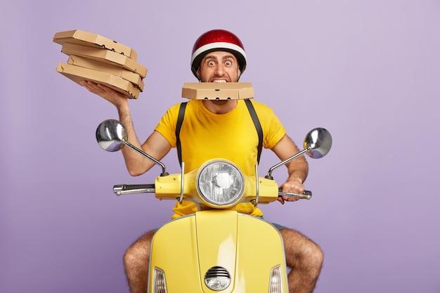 ピザの箱を持っている間黄色のスクーターを運転する面白い配達員 無料写真