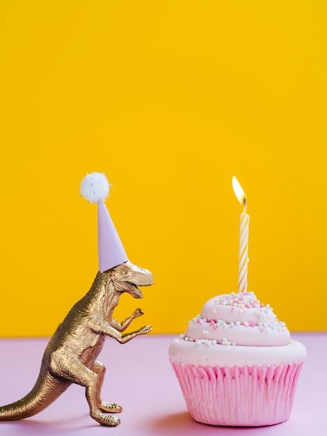 Dinosauro divertente con cappello compleanno e delizioso muffin Foto Gratuite