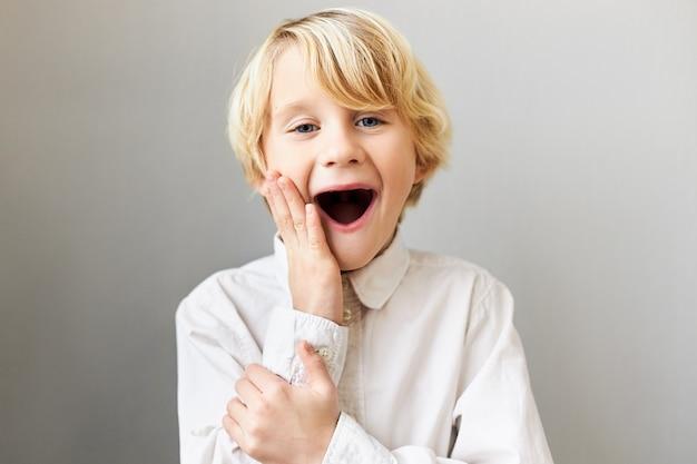 Divertente ragazzo europeo emotivo che esprime una vera reazione genuina, tenendo la bocca spalancata e toccando le guance, essendo eccitato con qualcosa, urlando wow. sorpresa e stupore Foto Gratuite