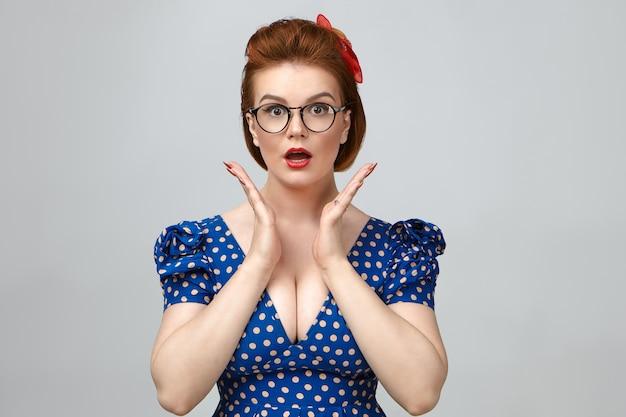 Divertente emozionale ragazza pin up che indossa rossetto rosso, abito scollato e occhiali da vista fissando la telecamera in stato di shock o stupore, eccitato con grandi prezzi di vendita o notizie positive, tenendosi per mano sul viso Foto Gratuite