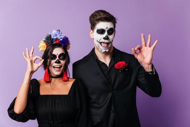 Забавные европейские молодые люди дурачатся на хэллоуин. крытый снимок смеющейся влюбленной пары в одежде зомби. Бесплатные Фотографии