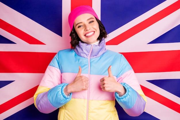 親のために海外の写真を作る面白い交換学生の女性は暖かい色のコート孤立したピンクの背景を着用します Premium写真