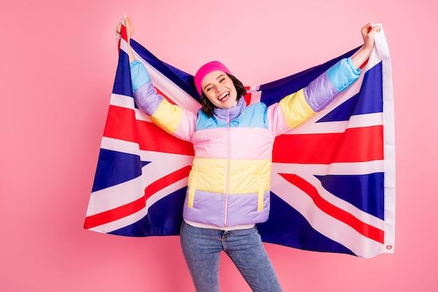 旗で写真を作る面白い交換学生の女性は暖かい色のコートの分離されたピンクの背景を着用します Premium写真