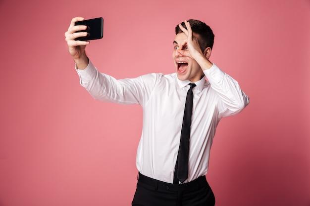Забавный взволнованный молодой бизнесмен делает селфи по мобильному телефону Бесплатные Фотографии