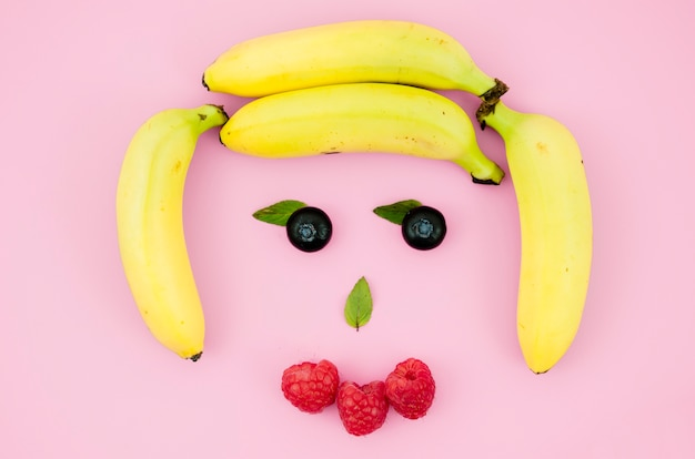 Funny face made from fruits and berries on light surface Free Photo