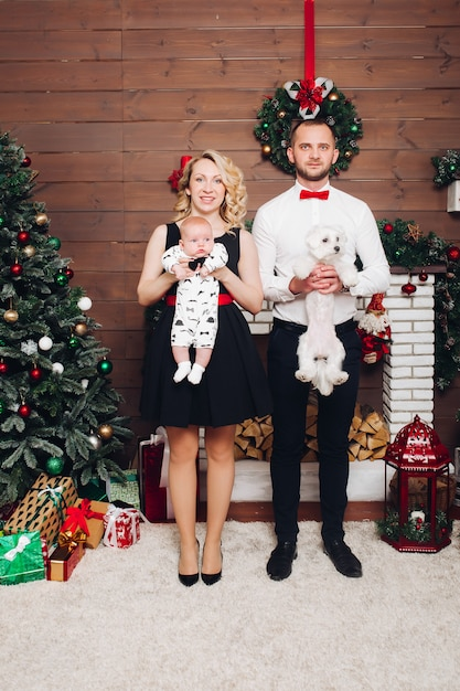 Funny family standing near fireplace holding dog and son in hands and smiling Premium Photo