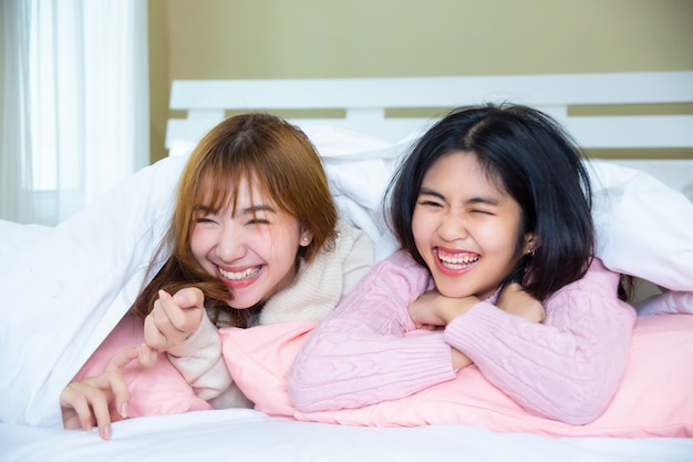 Funny friends lying under blanket with pillows on bed Free Photo