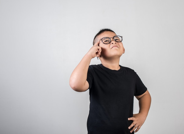 Funny genius boy thinking in studio shot Free Photo