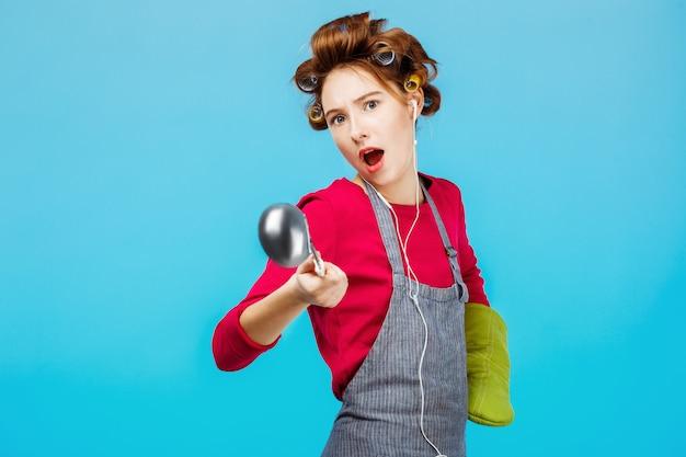 Смешная девчонка танцует во время приготовления ужина с зеленой перчаткой на руке Бесплатные Фотографии